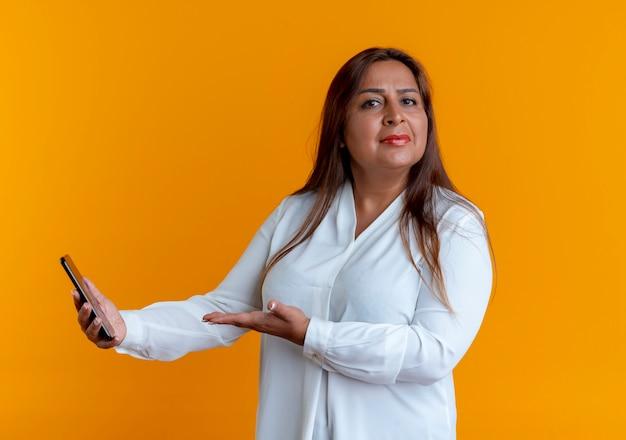Rigorosa casual caucasica donna di mezza età azienda e punti con la mano al telefono isolato sulla parete gialla
