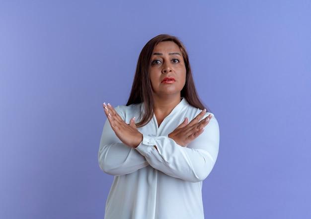 파란색 벽에 고립의 제스처를 보여주는 엄격한 캐주얼 백인 중년 여성