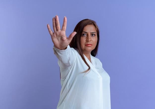 青い壁に隔離された停止ジェスチャーを示す厳格なカジュアルな白人の中年女性