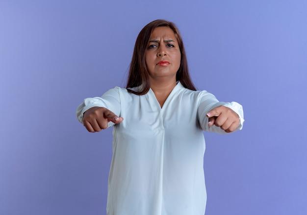 青い壁に隔離されたジェスチャーを示す厳格なカジュアルな白人の中年女性
