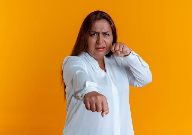 黄色の壁に隔離された戦闘ポーズで立っている厳格なカジュアルな白人の中年女性