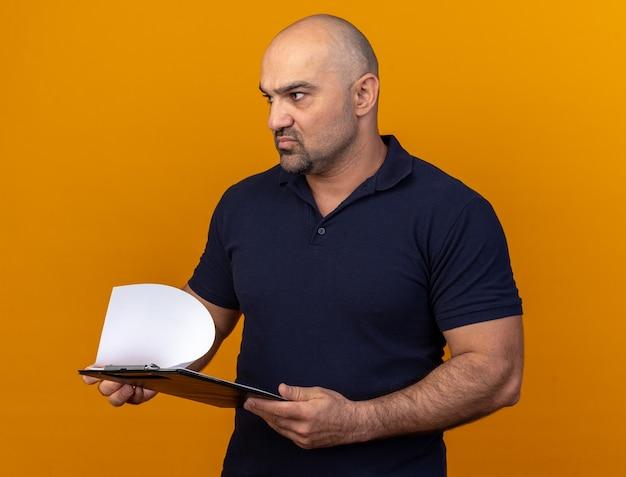 주황색 벽에 격리된 면을 보고 있는 클립보드를 들고 있는 엄격한 캐주얼 중년 남자