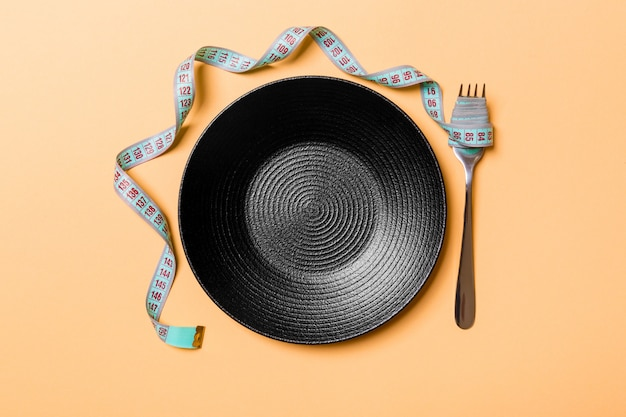 Strict diet  with empty space fro your design. top view of plate with fork in measuring tape on orange background