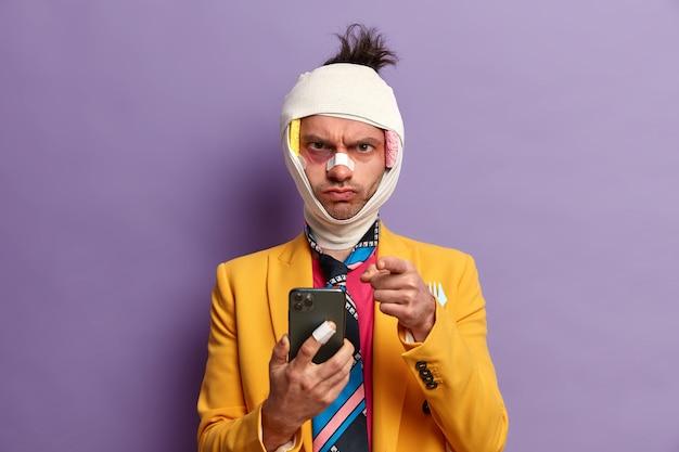 頭に包帯を巻いて、あなたを指さし、否定的な感情を表現し、顔に打撲傷を負い、現代の携帯電話を使用している、厳格な不快な男。負傷した戦闘機は彼のトラウマ、破損であなたを非難します
