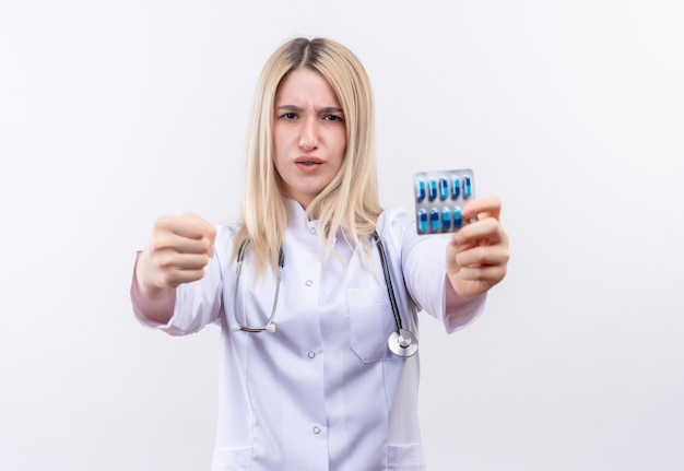 聴診器と孤立した白い背景の上のカメラで拳を保持している丸薬を保持している医療用ガウンを身に着けている厳格な医師の若いブロンドの女の子