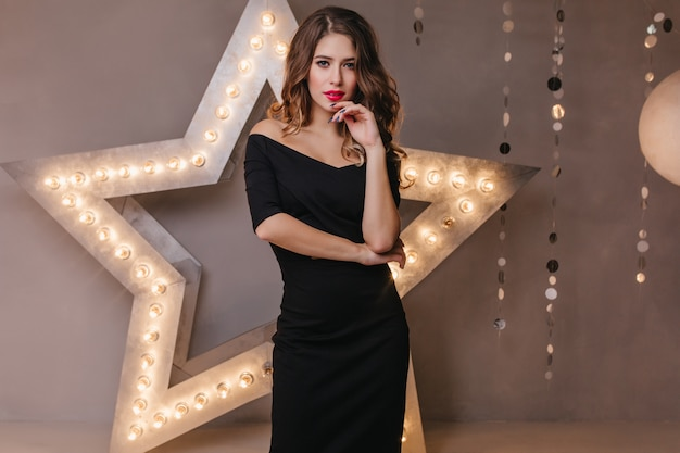 Strict, elegant lady in classic black dress confidently. woman posing  on wall of glowing stars