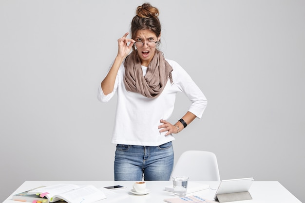 Strict female boss, looks angrily through glasses, going to shout
