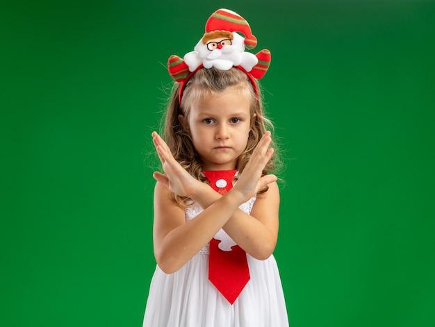 Bambina rigorosa che porta il cerchio dei capelli di natale con il legame che mostra il gesto di nessun isolato su fondo verde