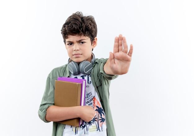 本を持って、白で隔離された停止ジェスチャーを示す厳格な小さな男子生徒