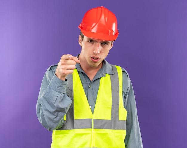 あなたにジェスチャーを示す制服を着たカメラの若いビルダーの男を厳密に見る