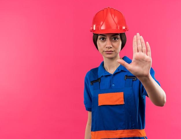 停止ジェスチャーを示す制服を着たカメラの若いビルダーの女性を厳しく見る