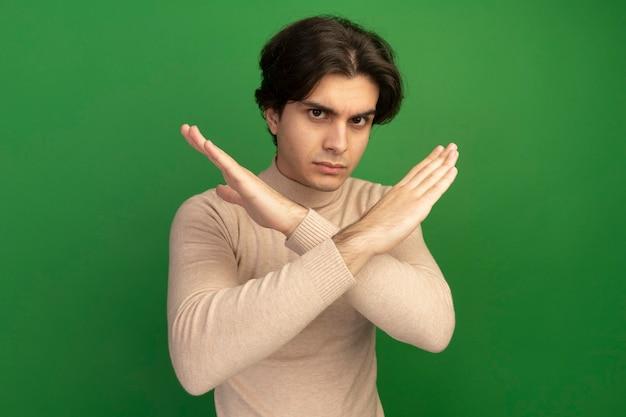 Строгий глядя на переднего молодого красивого парня, показывающего жест не изолированного на зеленой стене