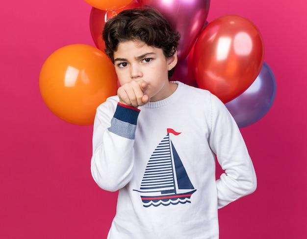분홍색 벽에 격리된 앞쪽 풍선 포인트 앞에 서 있는 엄격한 카메라 어린 소년