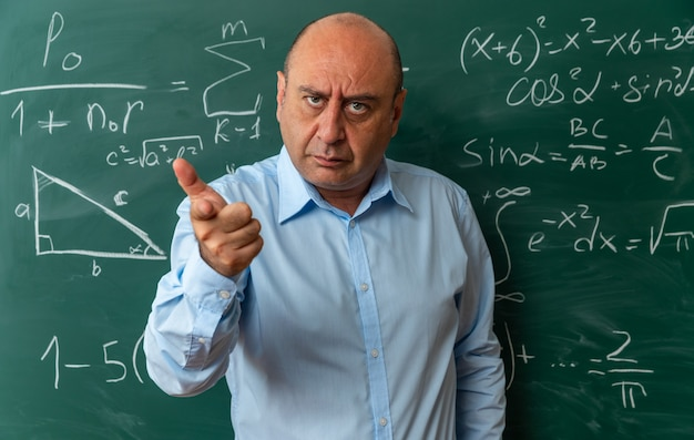 Rigoroso guardando la telecamera insegnante maschio di mezza età in piedi davanti alla lavagna che ti mostra il gesto