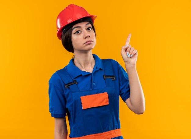 Rigoroso guardando la telecamera la giovane donna del costruttore in uniforme punta verso l'alto