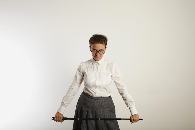 Strict looking conservatively dressed female teacher with a long black pointer on white wall