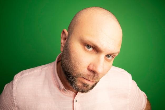 녹색에 고립 된 분홍색 티셔츠를 입고 엄격한 똑바로 중년 대머리 남자를 찾고