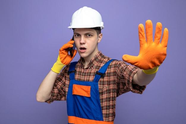 Il costruttore maschio rigoroso che indossa l'uniforme con i guanti parla al telefono