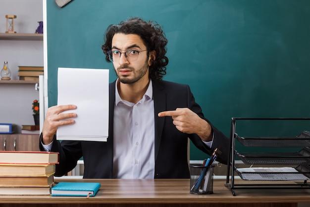 엄격한 남성 교사는 안경을 쓰고 교실에서 학교 도구를 가지고 테이블에 앉아 있는 종이를 가리킵니다.