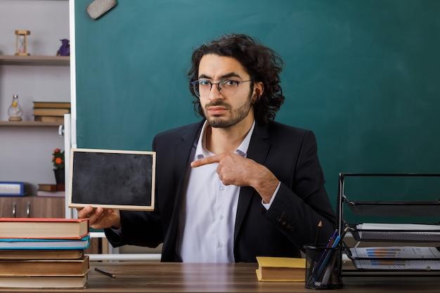 Insegnante maschio rigoroso con gli occhiali che tiene e indica la mini lavagna seduta al tavolo con gli strumenti della scuola in classe