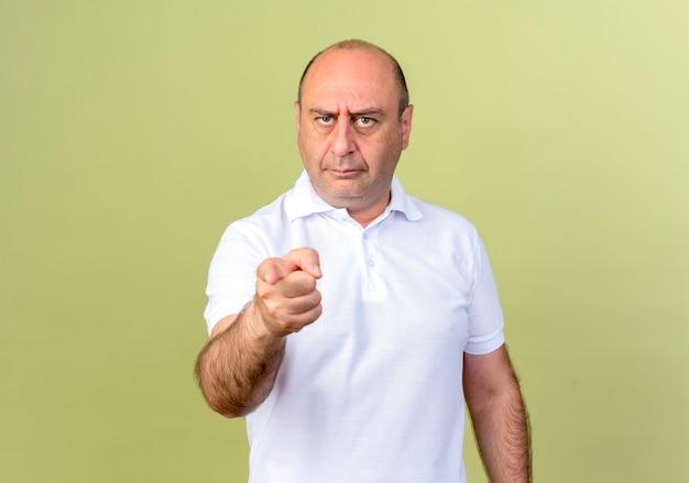 Строгий зрелый мужчина, показывающий вам жест, изолированный на оливково-зеленой стене