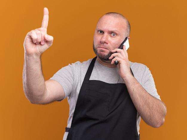 제복을 입은 엄격한 중년 남성 이발사는 오렌지 벽에 고립 된 전화 포인트에 말한다