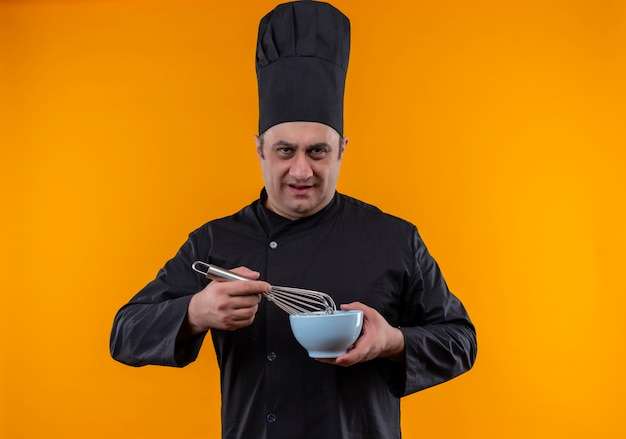 黄色の背景に泡立て器とボウルを保持しているシェフの制服を着た厳格な中年男性料理人