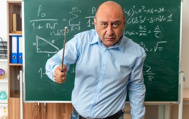 Insegnante maschio di mezza età rigoroso che sta davanti alla lavagna che tiene fuori il bastone del puntatore alla parte anteriore
