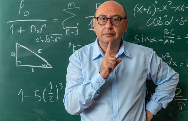 Insegnante maschio di mezza età rigoroso con gli occhiali in piedi davanti alla lavagna