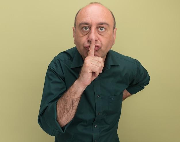 オリーブ グリーンの壁に隔離された沈黙のジェスチャーを示す緑の t シャツを着た厳格な中年男性