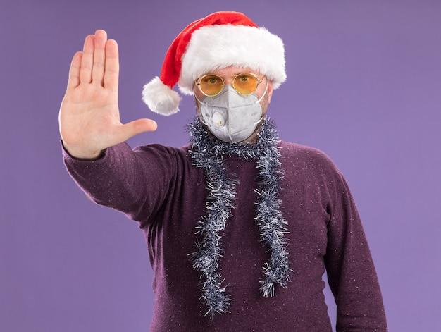 Rigoroso uomo di mezza età che indossa il cappello della santa e maschera protettiva con la ghirlanda di orpelli intorno al collo con gli occhiali che fa il gesto di arresto isolato sulla parete viola