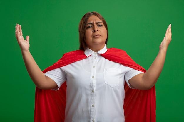 緑の背景に分離されたサイズを示す厳格な中年のスーパーヒーローの女性