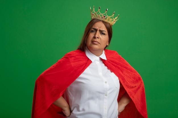 緑の背景で隔離の腰に手を置く王冠を身に着けている厳格な中年のスーパーヒーローの女性