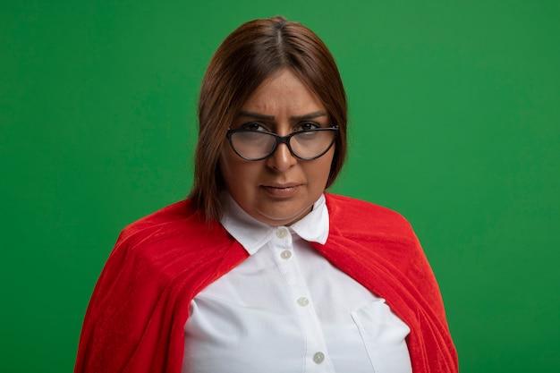 緑の背景に分離されたカメラを見て眼鏡をかけている厳格な中年のスーパーヒーローの女性