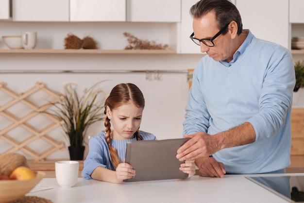 孫娘からタブレットを奪い、小さな子供を育てながら家に立っている厳格な古い引退した祖父