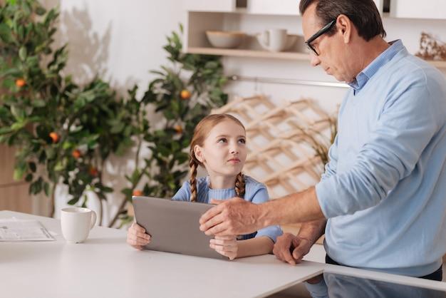 孫娘からデジタルガジェットを奪い、小さな子供を育てながら、家に立っている厳格なシニア自信のある祖父
