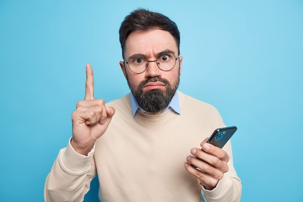 Strict serious bearded adult man raises index finger has excellent idea uses new mobile application holds smartphone wears spectacles and sweater