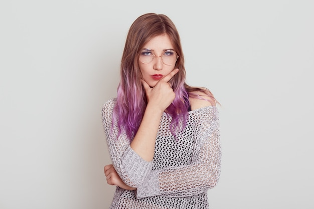 Rigorosa femmina seria con i capelli lilla che tiene le dita nel mento, pensa a cose o problemi importanti, indossa una camicia elegante, posa isolata sopra il muro grigio.