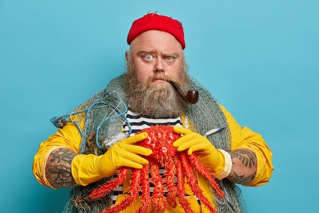 두꺼운 수염을 가진 엄격한 진지한 남자, 큰 붉은 게를 안고, 담배 파이프를 피우고, 항해와 크루즈를 즐기고, 빨간 모자를 쓰고, 어깨 너머로 낚시 그물을 즐깁니다.