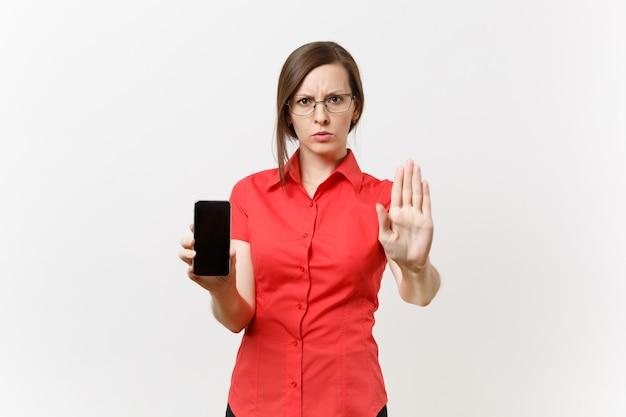 Строгая серьезная учительница в красной рубашке держит мобильный телефон с пустым пустым экраном, показывая стоп-жест с ладонью, изолированной на белом фоне. обучение преподаванию в концепции университета средней школы.