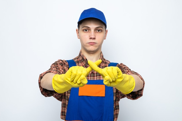 Strict showing gesture of no young cleaning guy wearing uniform and cap with gloves