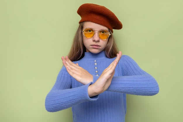 안경을 쓴 모자를 쓴 아름다운 어린 소녀의 엄격한 보여주는 제스처