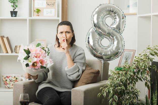 Rigoroso gesto di silenzio che mostra bella ragazza il giorno delle donne felici che tiene bouquet seduto sulla poltrona in soggiorno