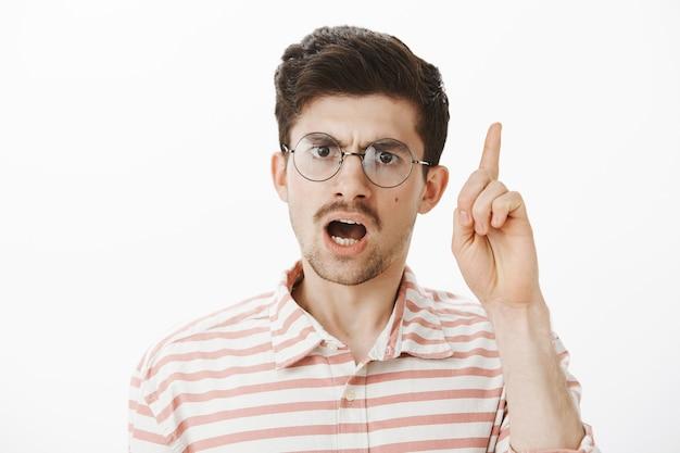 厳格な教師が生徒の悪い行動を叱る。口ひげを持つ深刻な集中型のひげを生やした男性のショット、人差し指を上げて発言し、主張し、灰色の壁の上に不快に立っています。