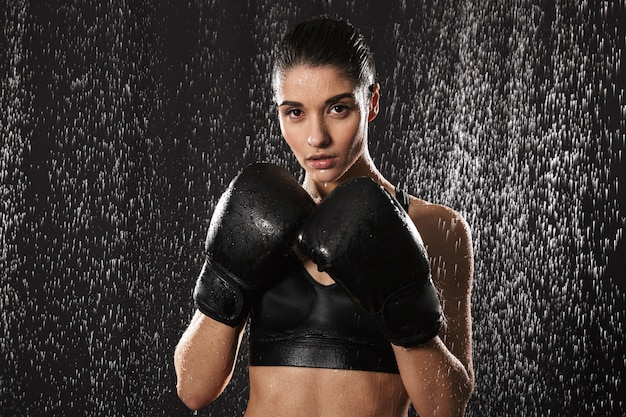 Strict woman doing sports and boxing in gloves while standing in defense position under rain drops, isolated over black background
