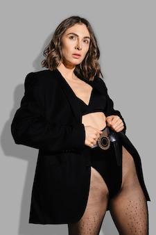 재킷에 엄격한 여자가 허리에 스타킹을 당깁니다.