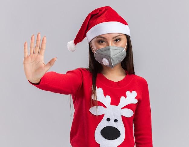 Rigorosa giovane ragazza asiatica che indossa il cappello di natale con maglione e mascherina medica che mostra gesto di arresto isolato su sfondo bianco