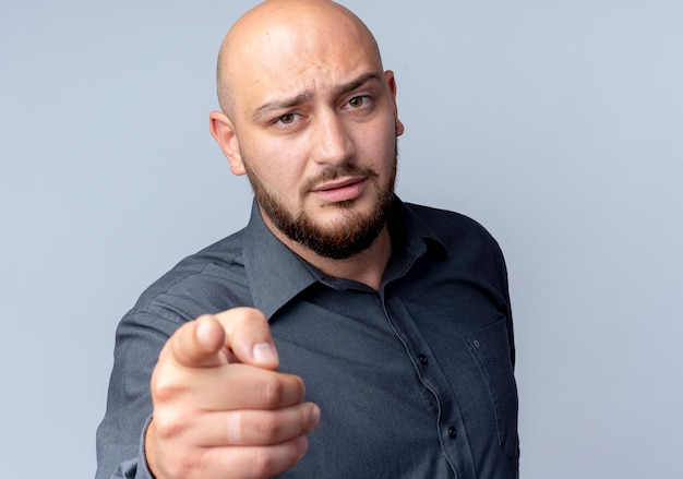 Strict young bald call center man pointing and looking at front isolated on white wall