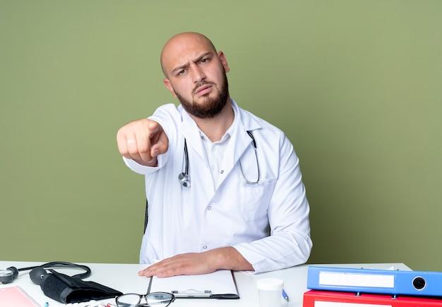 의료 가운과 청진기를 입고 엄격한 젊은 대머리 남성 의사는 녹색 벽에 고립 된 제스처를 보여주는 의료 도구와 책상 작업에 앉아
