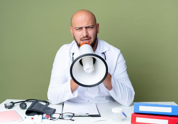 Строгий молодой лысый врач-мужчина в медицинском халате и стетоскопе сидит за столом